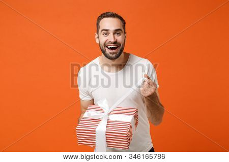 Joyful Young Man In White T-shirt Posing Isolated On Orange Background. Valentines Day Womens Day, B