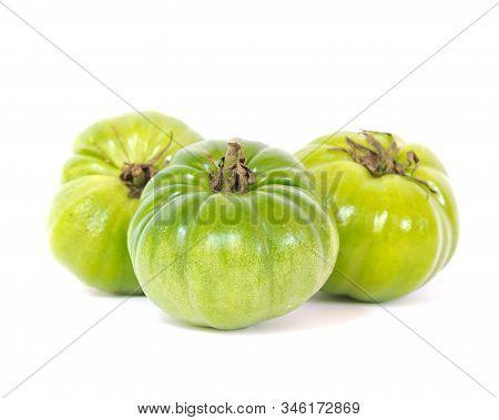 Three Unripe Organic Heirloom Beefsteak Tomatoes Isolated On White