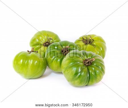 Heap Of Unripe Organic Heirloom Beefsteak Tomatoes Isolated On White