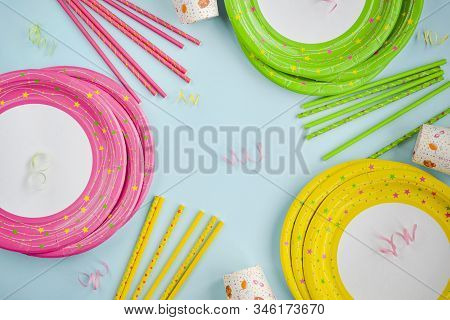 Colorful Yellow, Green, Pink Paper Plates, Cup, Straw.decoration With Paper Ribbons On A Blue Backgr