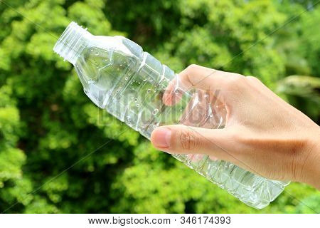 Hand Holding An Empty Plastic Bottle Of Drinking Water With Blurry Green Foliage In The Backdrop
