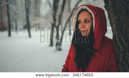 Portrait Of Young Woman In Red Jacket And Hood In Winter Season. Beautiful Lady Stands Near Tree And