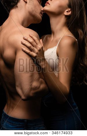 Side View Of Undressed Sexy Young Couple In Jeans Embracing And Kissing Isolated On Black