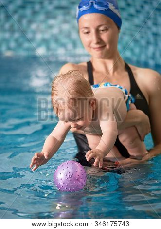Close-up Snapshot Of Mother Holding Her Baby Boy In Her Arms In Indoor Pool. Blonde Kid Is Trying To