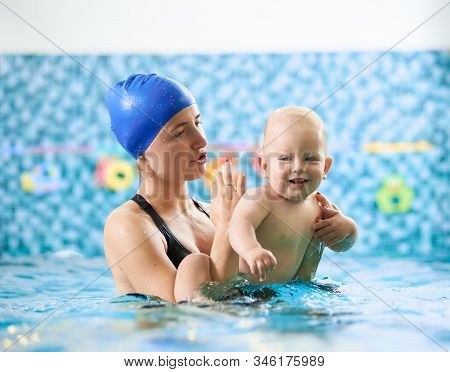 Swimming Class For Infants. Young Mother Supporting Her Baby In Swimming Pool And Giving Instruction