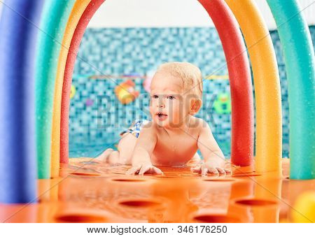 Very Cute Interesting Little Boy Is Lying On His Belly On A Floating Colorful Construction In The Sw