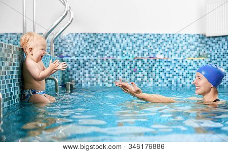 Side View Snapshot Of Mother And Son Spending Fun Time In Swimming Pool, Happy Woman Reaching Out He