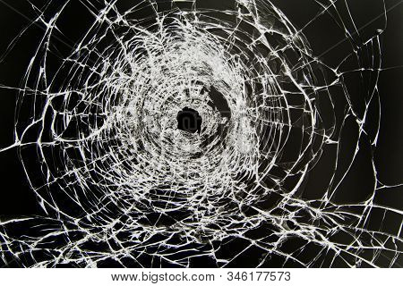 Texture Of Cracked Broken Glass With A Hole, Cracked By Impact. Concept Shot In The Window On A Blac