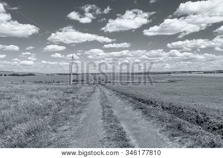 Unpaved Rural Road Through The Field, On A Sunny Day.