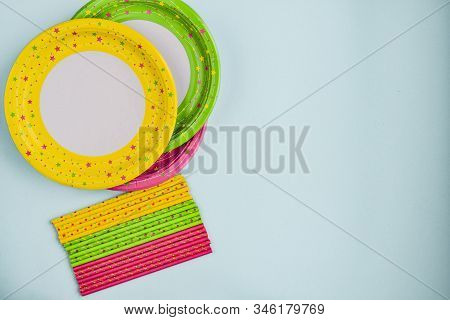 Colorful Yellow, Green, Pink Paper Plates, Boiler Tubes. Decoration With Paper Ribbons On A Blue Bac