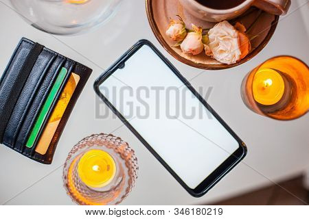 A Phone With A White Screen On A Glass Table Decorated With Candles Next To A Wallet And A Cup Of Co