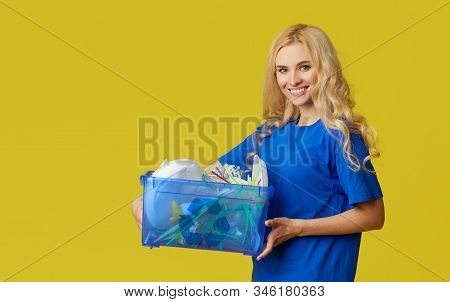 Caring For Nature. Young Woman In A Blue T-shirt Are Holding A Box With Plastic Bottles And Waste. V