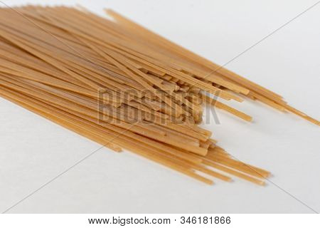 Long Flat Brown Macaroni On A White Background.