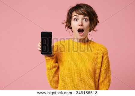Shocked Young Brunette Woman Girl In Yellow Sweater Posing Isolated On Pastel Pink Background Studio