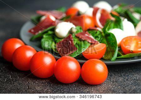 Salad With Prosciutto, Mozzarella, Fresh Vegetables On A Dark Plate On A Black Background.