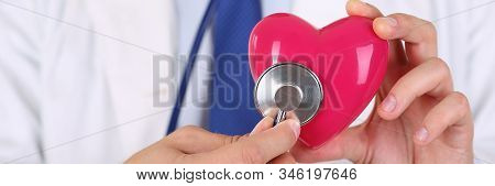 Male Medicine Doctor Holding Red Heart And Putting Stethoscope Head Close To It Closeup. Medical Hel