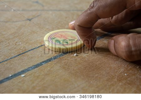 Person Ready To Strike The Coins In Carrom Board Game. Multiplayer Board Game With Good Fun Time.