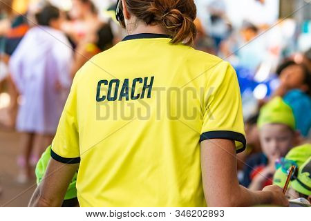 Back View Of A Female Coach Wearing Bright Green Coach Shirt With The Word Coach Printed On Back
