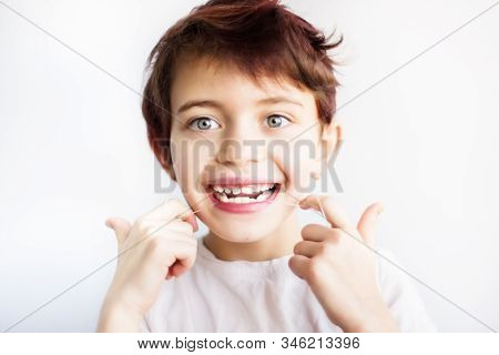 Horizontal Portrait Of 7 Years Old Smiling Child In White T-shirt Flossing His Teeth On White Backgr