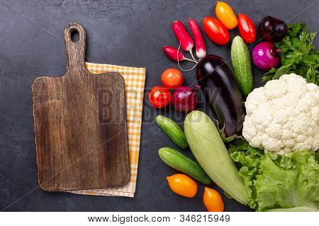 Brawn Cutting Board And Fresh Farmers Garden Vegetables On Wooden Table. Harvest Time. Top View - Im