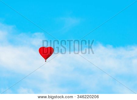 St Valentines day background. Red balloon in the the shape of heart in the blue sky. St Valentines day landscape, romantic adventure background with love and St Valentines day concept