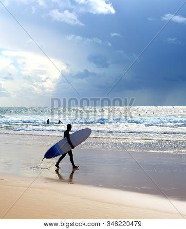 Surfer With Surfboard On The Beach. Rain In The Ocean. Algarve, Portugal