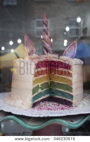 The Multi-colored Cake In Layers In The Shape Of A Unicorn In A Store Window. Sold In Pieces.