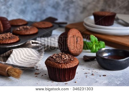 Chocolate Muffins With Chocolate Moss Sauce And Mint On A Concrete Background.