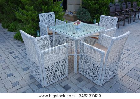 Chairs And Tables Of A Restaurant Seating Outside With Parasols.garden Terrace White Table Set Up Fo