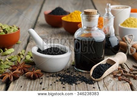 Black cumin or roman coriander seeds, black caraway oil bottles and aromatic spices and herbs: turmeric, cardamom, cinnamon, cloves, anise, paprika. Ingredients for cooking. Ayurveda treatments.