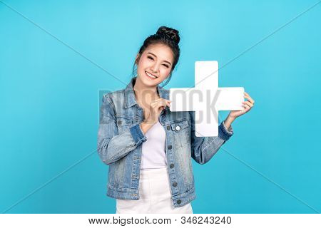 Happy Asian Woman Smiling And Holding Plus Or Add Sign On Blue Background. Cute Asia Girl Smiling We