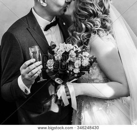 Close Up. Bride And Groom With Glasses Of Champagne Kissing Each Other.