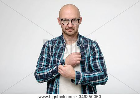 Serious Bald, Unshaven Man With Glasses Fastens A Button On A Shirt Cuff And Looks Confidently At Th