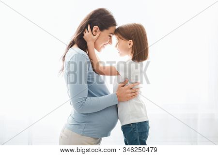 Loving Little Daughter Embracing Her Expecting Young Mother, Looking At Her Eyes, Side View, Window