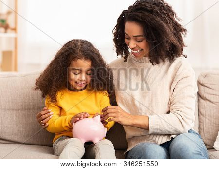 Family Savings. Cheerful Afro Mother Teaching Little Daughter How To Save Money Holding Piggybank Si