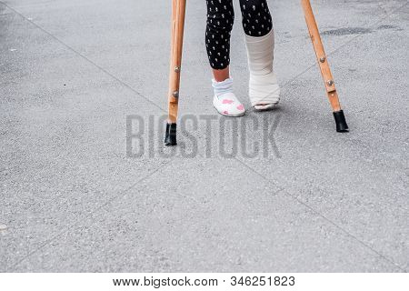 Child Using Crutches And Broken Legs For Walking Outdoor, Close Up. Broken Leg, Wooden Crutches, Ank