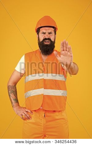 Caution, Under Construction. Hard Worker Showing Caution Sign On Yellow Background. Bearded Man With