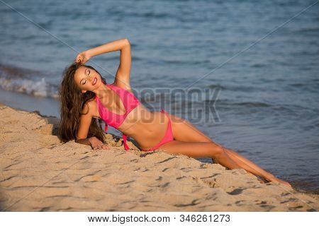 Beautiful Girl In A Pink Swimsuit On The Ocean. Bright Smile. Beautiful Tan.