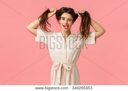 Funny And Playful Carefree Young Goofy Girl Showing Tongue And Smiling, Wink Camera Happily, Pulling