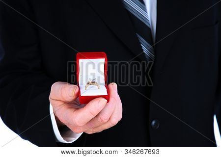 Engagement Ring. Wedding Ring. Friendship Ring. A man in a suit holds a Diamond Ring. Isolated on white. Room for text. clipping path. People world wide enjoy Wedding Rings. Jewelry & Valentines Day.