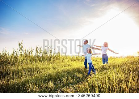 Photo A Happy Family In White T-shirts, Sunglasses And Jeans In The Park Spread Apart Arms Mimicking