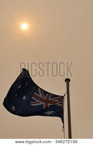 Australian Flag Flying Against Hazy Sky With Sun