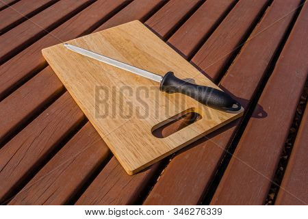 Honing Steel On Woodblock Cutting Board On Picnic Table.