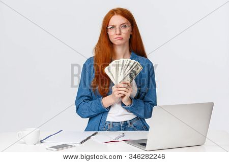 Thoughtful And Hesitant Serious-looking Redhead Female Got Payed, Won Big Money Prize In Online Art
