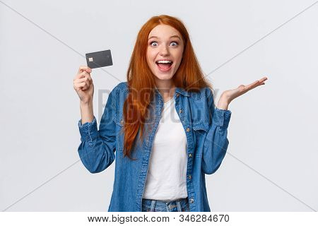 Waist-up Portrait Surpirsed And Cheerful Redhead Girl Talking About Bank Service, Holding Credit Car