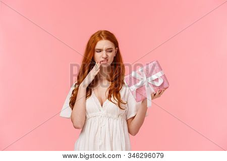 Picky And Ignorant Displeased Spoilt Redhead Girl, Holding Wrapped Cute Box With Gift, Looking With