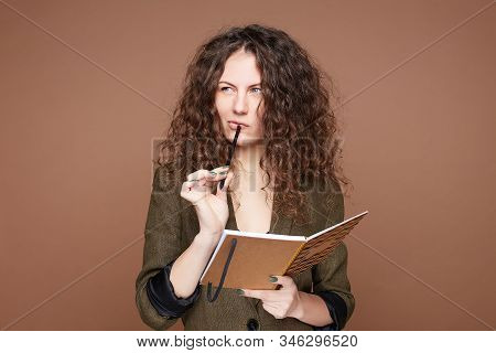 Pensive Confused Curly Haired Woman Purses Lips In Bewilderment, Writes Notes In Notepad, Thinks On