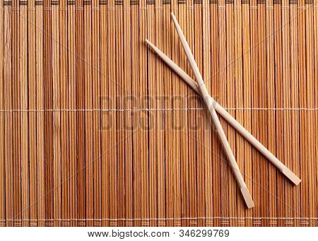 Chopsticks On A Wooden Table Surface Close-up. Chopsticks On Wooden Background Top View. Two Wooden