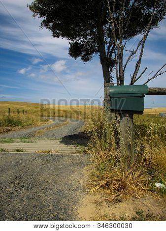 Bendy driveway to enter a farmland with picturesque hills in the background. Summer in Australia is
