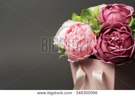 Flowers In Bloom: Bouquet Of Lilac And Pink Peonies In A Pink Square Box On A Gray Background.
